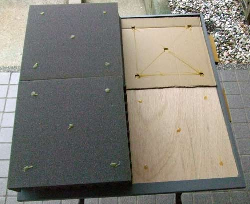 The acoustic panel showing two foam tiles with glue on, and the template used to make sure the glue on the tile aligns with the glue on the base.