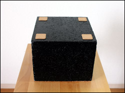 Black-painted concrete with stick-on cork feet at the base.
