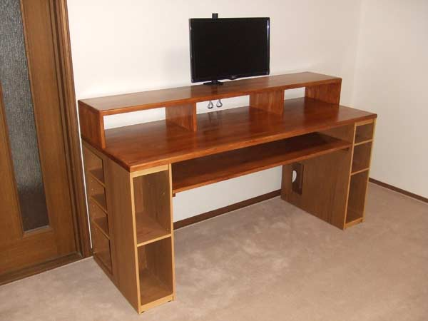 The oak-colured desk assembled in a room with a beige carpet and white walls.