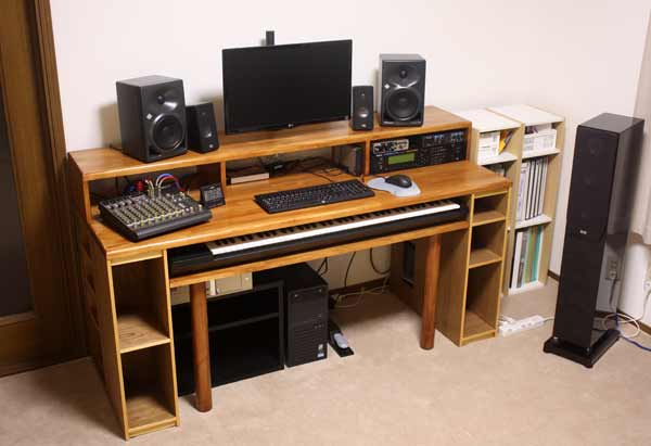 The desk fully assembled with monitors, mixer, computer screen and keyboard all in position.