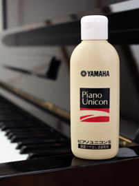 Image of a bottle of piano polish standing on the edge of a piano, with part of the piano keyboard visible in the background.