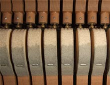 The hammers inside an upright piano, showing wear.