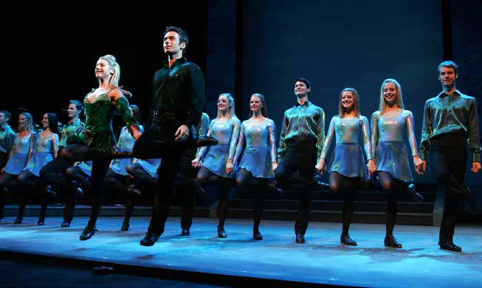 A view of the Riverdance dance troupe on stage, performing an Irish dance.