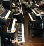 Six keyboards on stands in a shop.